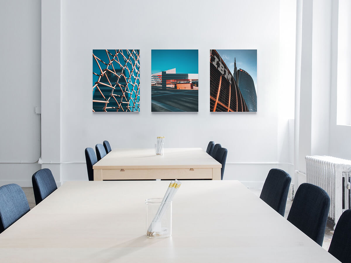Three canvas prints above two meeting tables