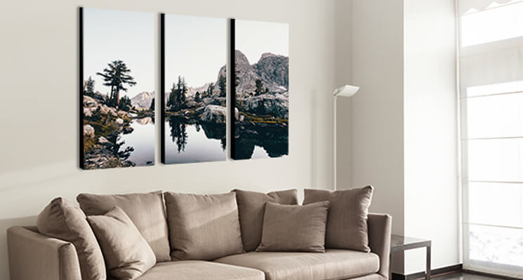A triptych canvas print displayed over a couch.