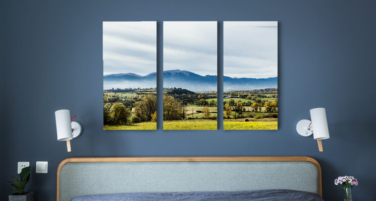 A triptych canvas print displayed over a bed.